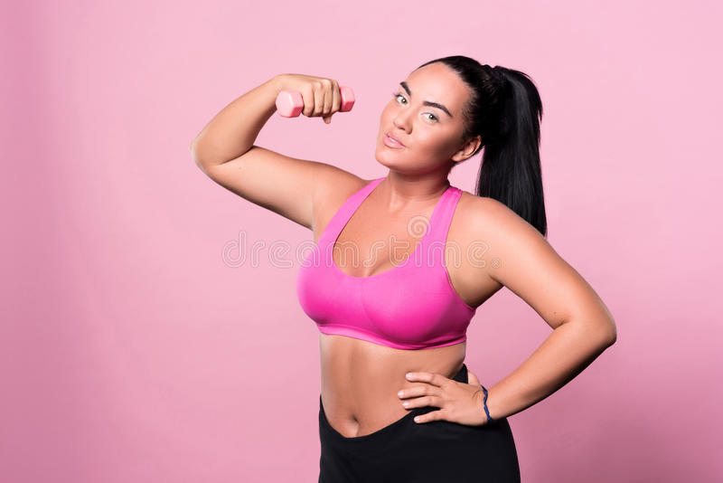 Pretty plump woman posing with small dumbbell royalty free stock image