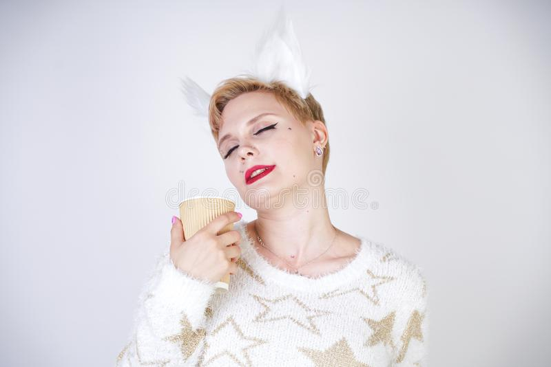 Pretty plus size caucasian woman wearng fashion knitted warm sweater and fur cat ears and posing on white studio background alone royalty free stock images