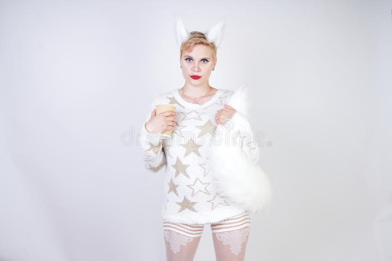 Pretty plus size caucasian woman wearng fashion knitted warm sweater and fur cat ears and posing on white studio background alone stock photos
