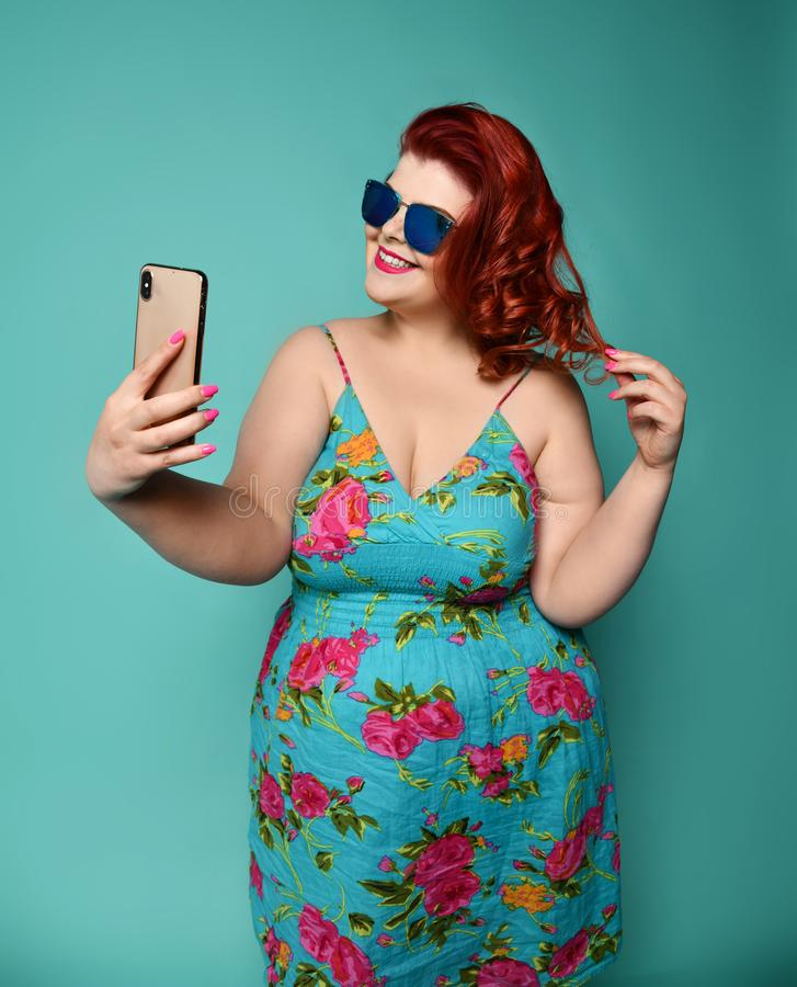 Pretty plus-size fat woman with hollywood smile in fashion sunglasses and colorful clothes does fashion selfie on mint stock image