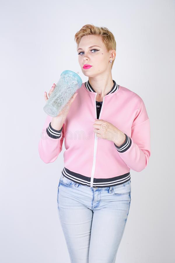 Pretty plus size short hair woman with blue cup of water. blonde adult girl wearing sport pink jacket and jeans posing on white st. Udio background alone stock image