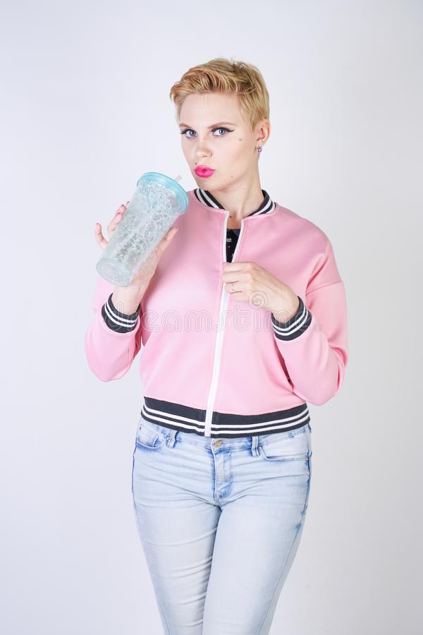 Pretty plus size short hair woman with blue cup of water. blonde adult girl wearing sport pink jacket and jeans posing on white st. Udio background alone stock images