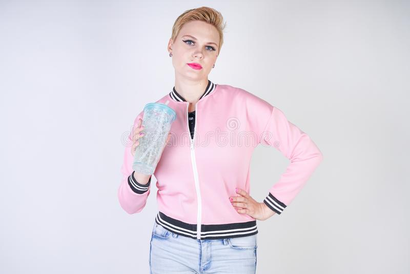 Pretty plus size short hair woman with blue cup of water. blonde adult girl wearing sport pink jacket and jeans posing on white st. Udio background alone royalty free stock image