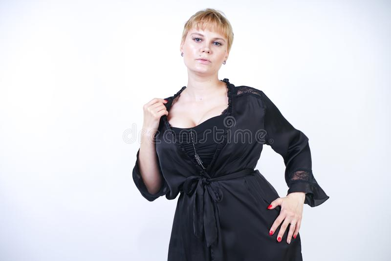 Pretty plus size woman with short hair and chubby curvy body wearing retro bodysuit underwear and posing on white studio backgroun stock photo