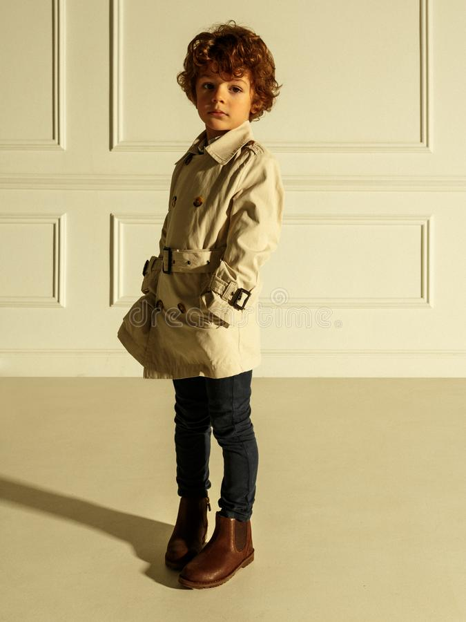 Pretty portrait of a curly little boy in stylish clothing, with hands in his pocket, isolated on a beige background stock photos