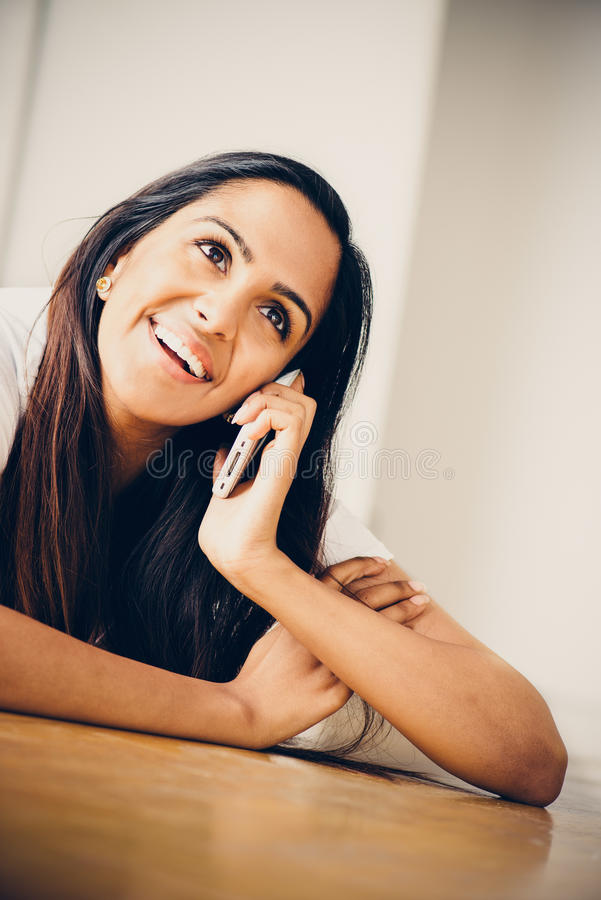Pretty portrait Indian teenager using mobole phone. Pretty Indian teenager using mobile phone smiling royalty free stock photography