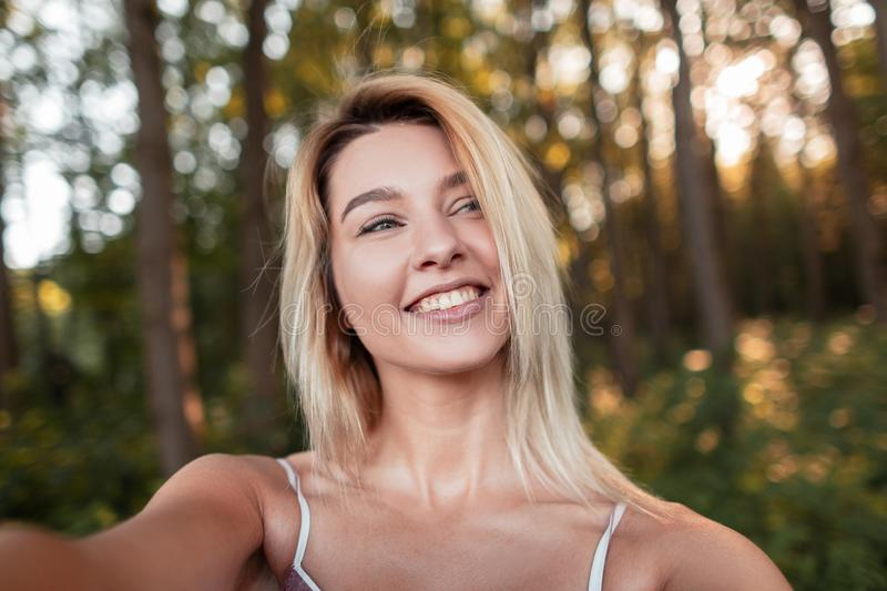 Pretty positive young blond woman with a beautiful smile with blue eyes makes a selfie in the forest on a sunny summer day. stock photos