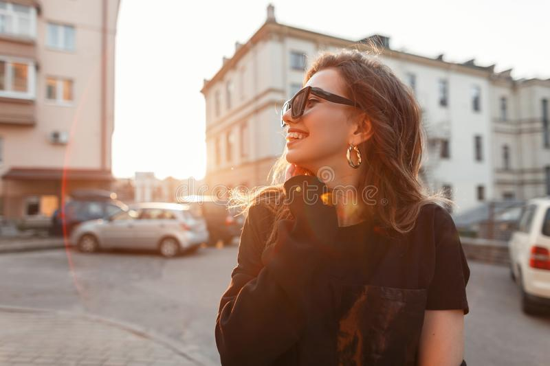 Pretty positive young hipster woman in stylish T-shirt in dark trendy sunglasses is standing and smiling outdoors near buildings stock photography