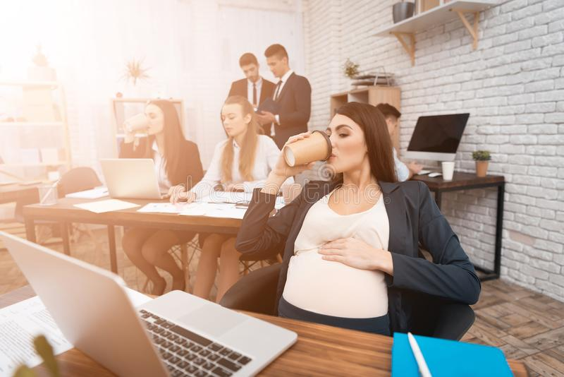 Pretty pregnant woman drinks cup of coffee at workplace. Pregnant girl is holding her pregnant belly. stock images