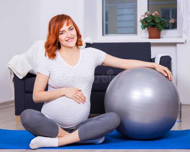 Pretty pregnant woman exercising with fitness ball at home stock image