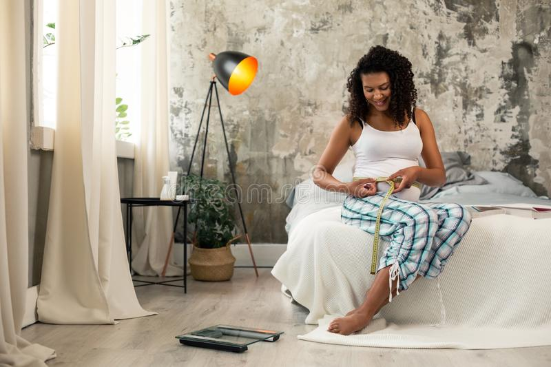 Pretty pregnant woman sitting on her bed. stock photography