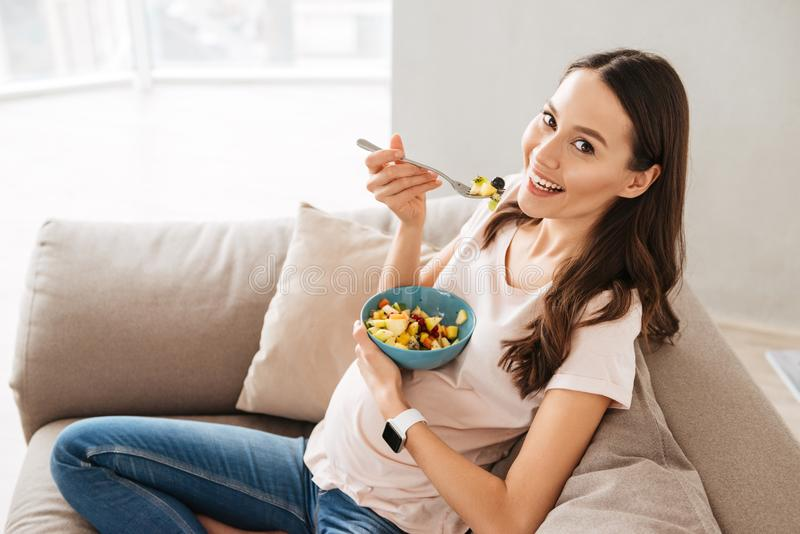 Pretty pregnant young woman having healthy breakfast. While sitting on a couch royalty free stock images