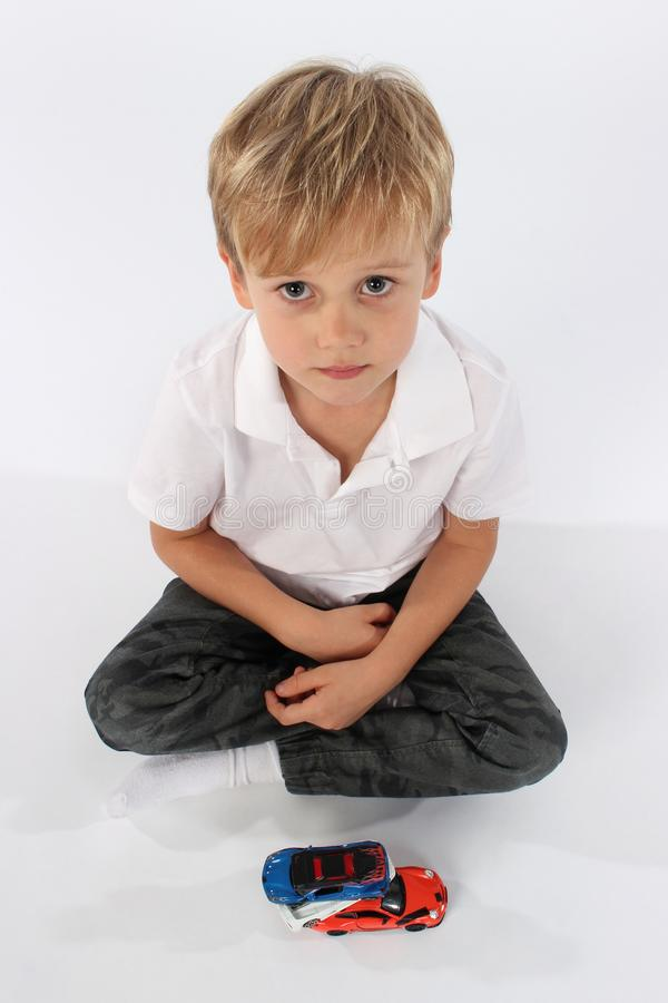 Pretty preschool boy sitting with a set of toys and wondering, what now? stock photo