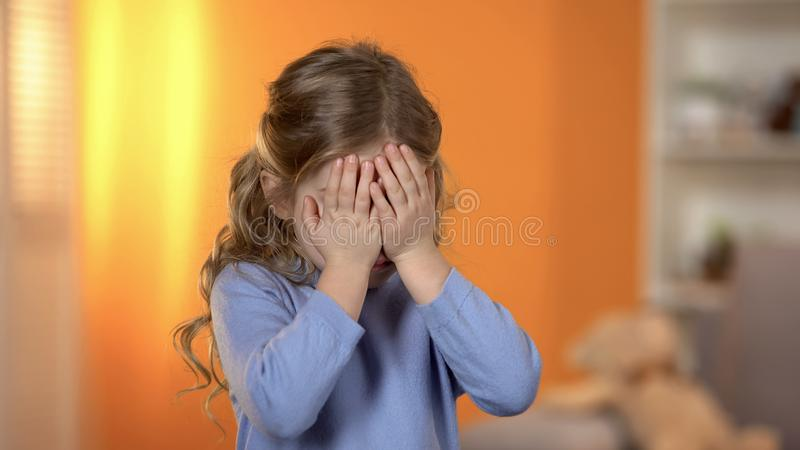 Pretty preschool girl closing eyes with hands, suffering bullying, friends lack royalty free stock image