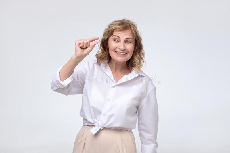 Pretty puzzled mature woman shows something invisible with her fingers. stock images