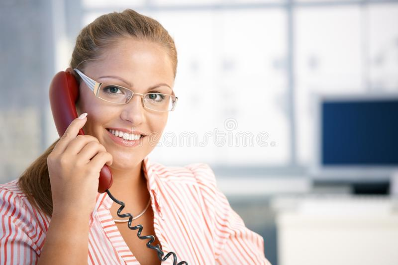 Pretty receptionist working talking on phone. Pretty receptionist working in office, talking on phone, smiling stock image
