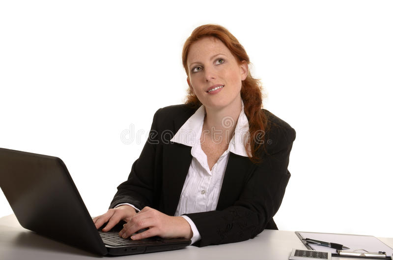 Pretty red-haired business woman thinking in office royalty free stock photo