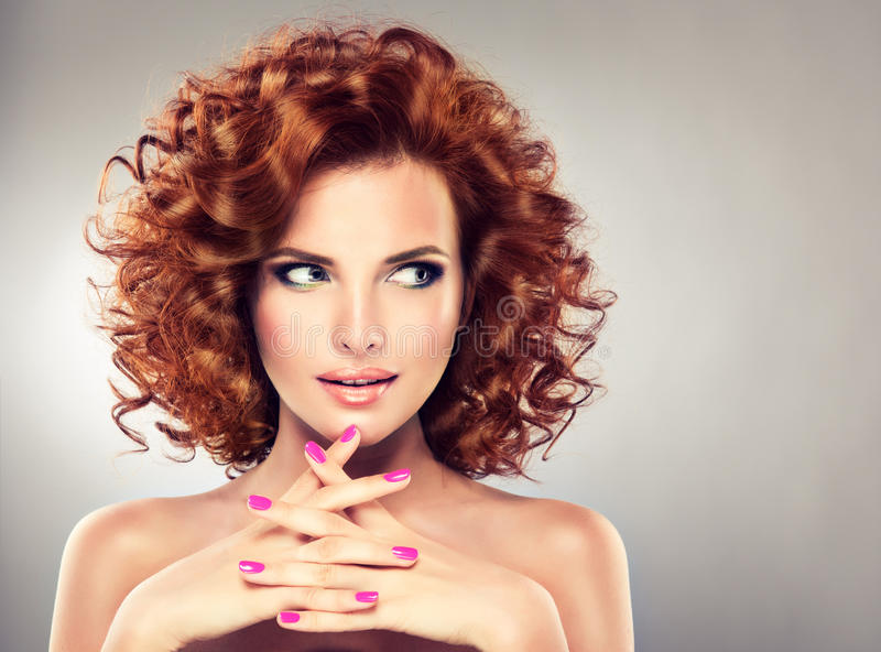 Pretty red haired girl with curls. Pretty red haired girl with curls , fashionable makeup and pink manicure. Tricky glance stock photography