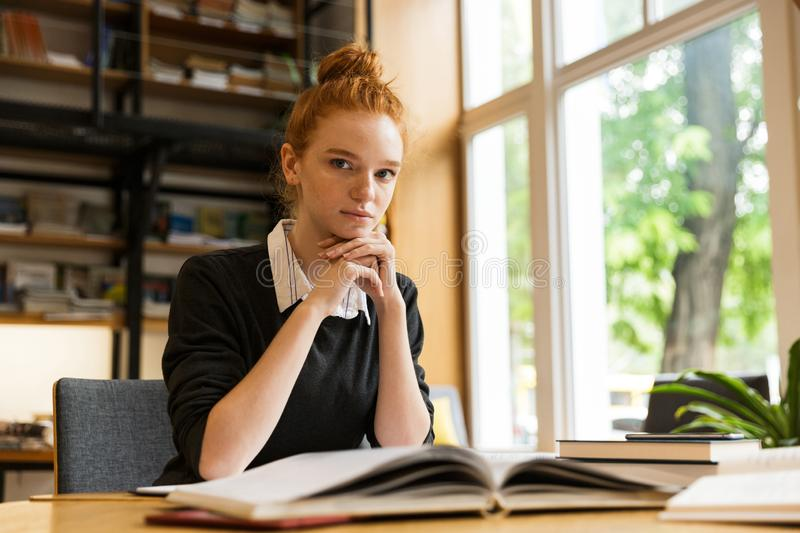 Pretty red haired teenage girl studying at the table royalty free stock photo