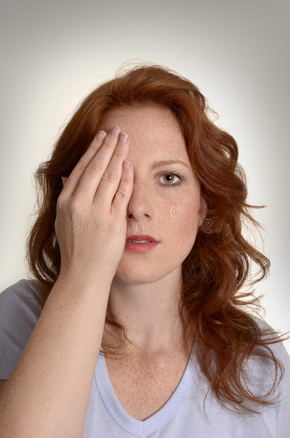 Pretty red-haired woman holds hand before eyes royalty free stock photo