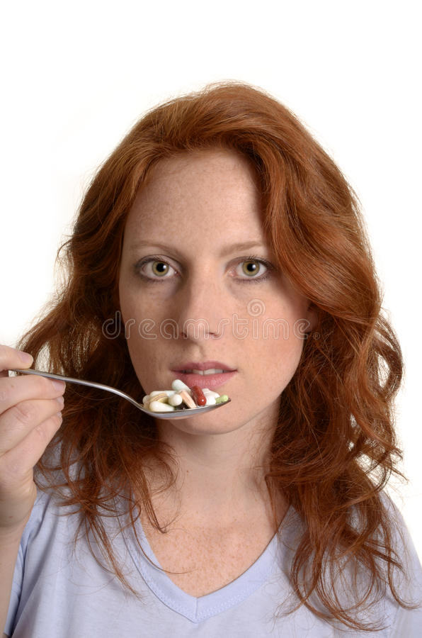 Pretty red-haired woman with spoon full of pills stock photo