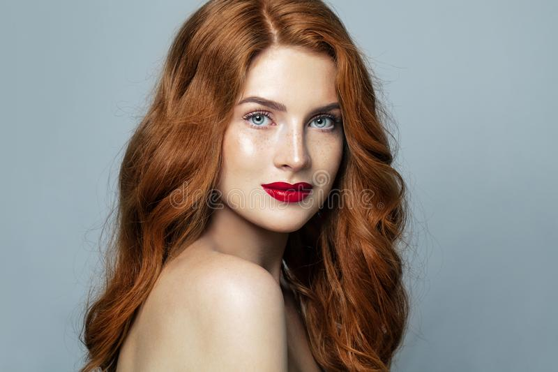 Pretty red haired woman studio portrait. Redhead girl smiling stock image