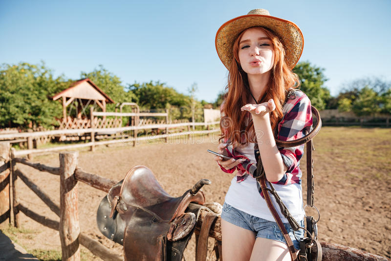 Pretty redhead cowgirl in straw hat sending air kiss. While sitting on the fence royalty free stock image