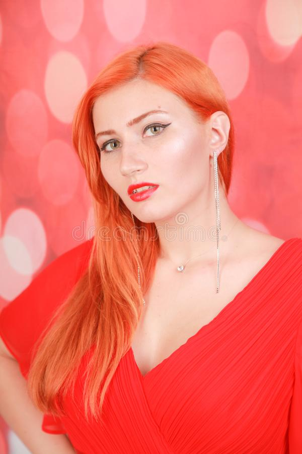 Holiday woman in red dress over christmas studio background. Pretty redheaded woman in fashion red dress celebrate christmas royalty free stock photos