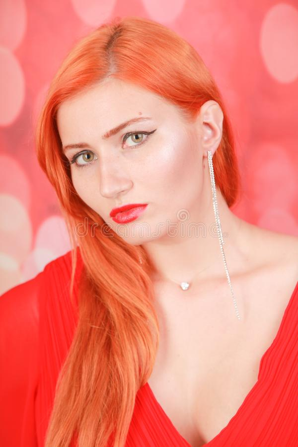 Holiday woman in red dress over christmas studio background. Pretty redheaded woman in fashion red dress celebrate christmas royalty free stock photography