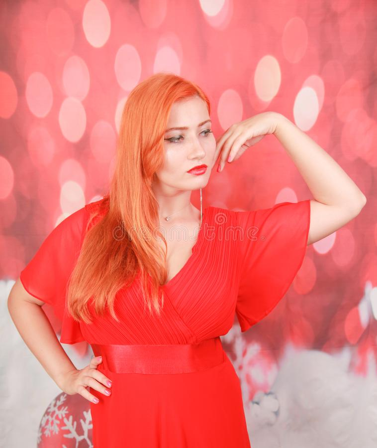 Holiday woman in red dress over christmas studio background. Pretty redheaded woman in fashion red dress celebrate christmas stock photos