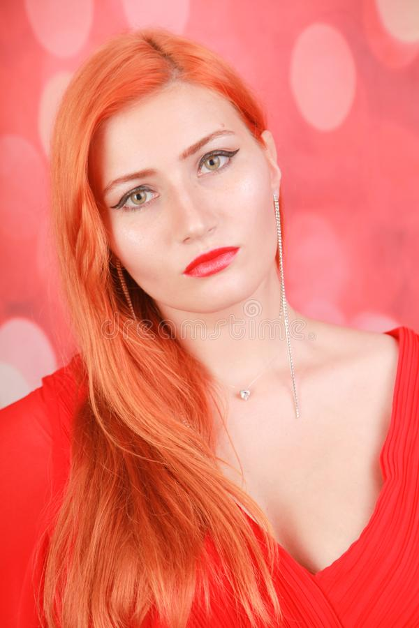 Holiday woman in red dress over christmas studio background. Pretty redheaded woman in fashion red dress celebrate christmas stock images