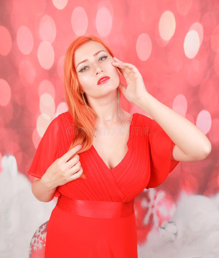 Holiday woman in red dress over christmas studio background. Pretty redheaded woman in fashion red dress celebrate christmas stock photography