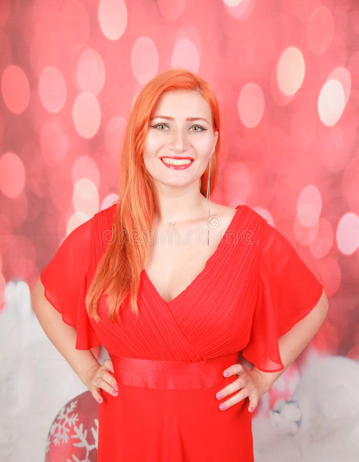 Holiday woman in red dress over christmas studio background. Pretty redheaded woman in fashion red dress celebrate christmas royalty free stock images