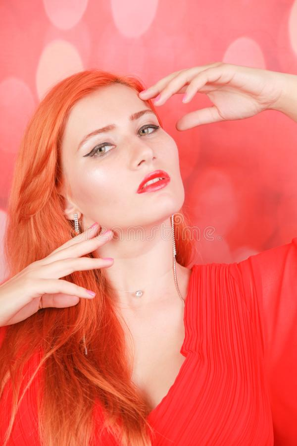 Holiday woman in red dress over christmas studio background. Pretty redheaded woman in fashion red dress celebrate christmas stock photo