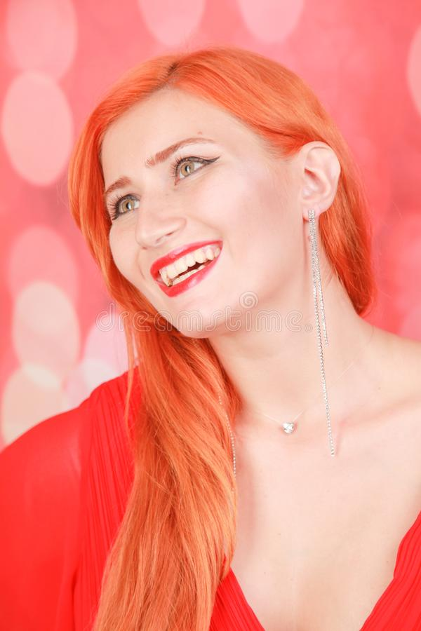 Holiday woman in red dress over christmas studio background. Pretty redheaded woman in fashion red dress celebrate christmas stock image