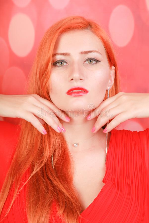 Holiday woman in red dress over christmas studio background. Pretty redheaded woman in fashion red dress celebrate christmas royalty free stock photo