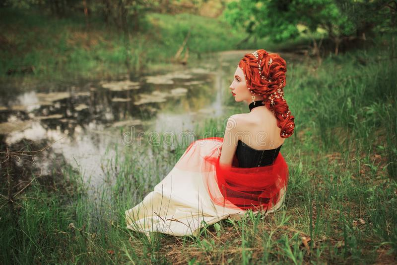 Pretty renaissance princess with hairstyle on picturesque lake background. Rococo queen sit on grass. Pretty princess on. Picturesque nature background stock images