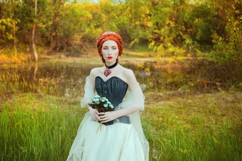 Pretty renaissance princess in red necklace with hairstyle on nature background. Rococo queen in necklace on neck. Pretty princess. With flower bouquet on stock image