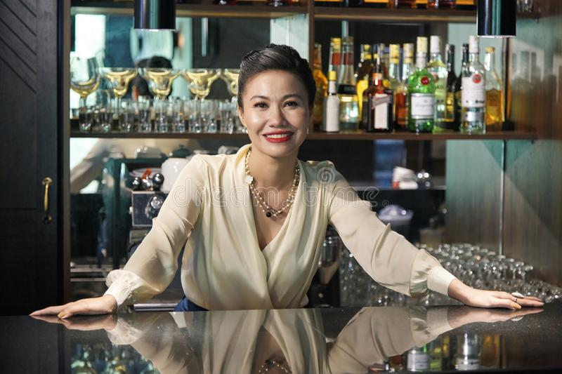 Pretty restaurant owner. Portrait of smiling pretty restaurant owner standing at bar counter royalty free stock photography