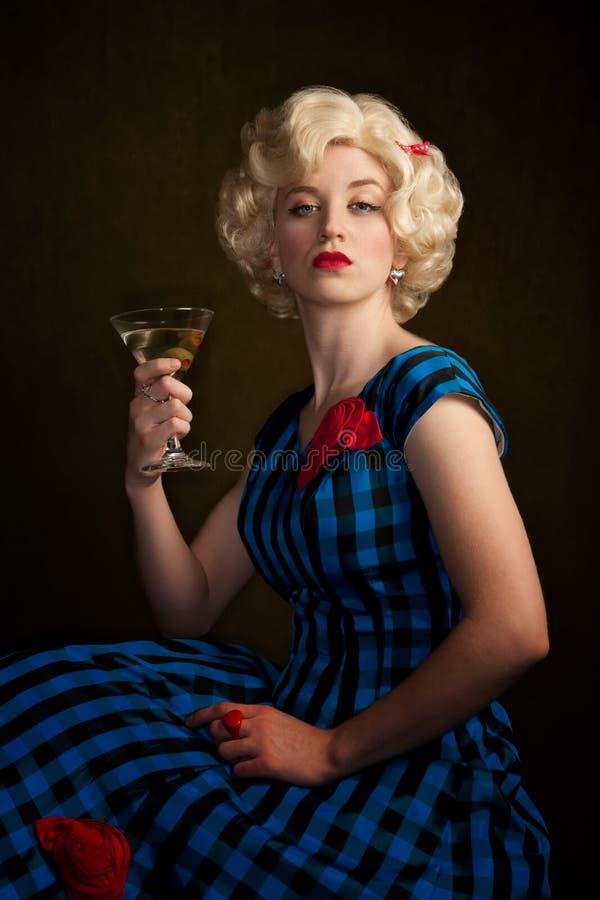 Pretty Retro Blonde Woman with Martini. Pretty retro blonde woman in vintage 50s dress with martini stock photography