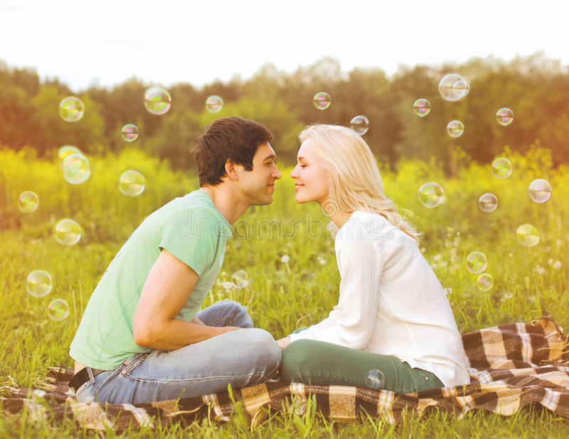 Pretty romantic couple in love having fun soap bubbles stock images