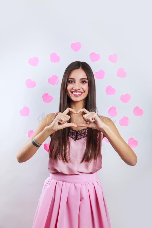 Pretty romantic young brunette indian woman making a heart gesture with her fingers in front . Valentines day concept stock image