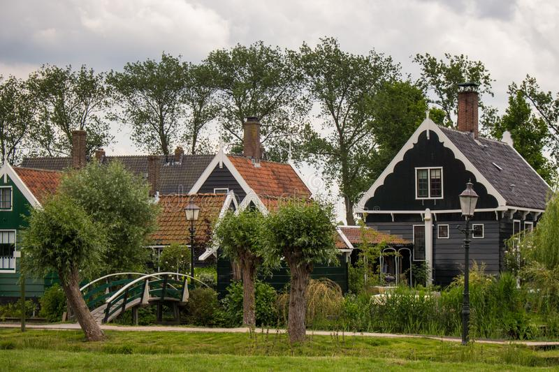 Pretty rural buildings with wooden bridge and trees. Idyllic countryside landscape. Typical holland houses with vintage bridge. royalty free stock images