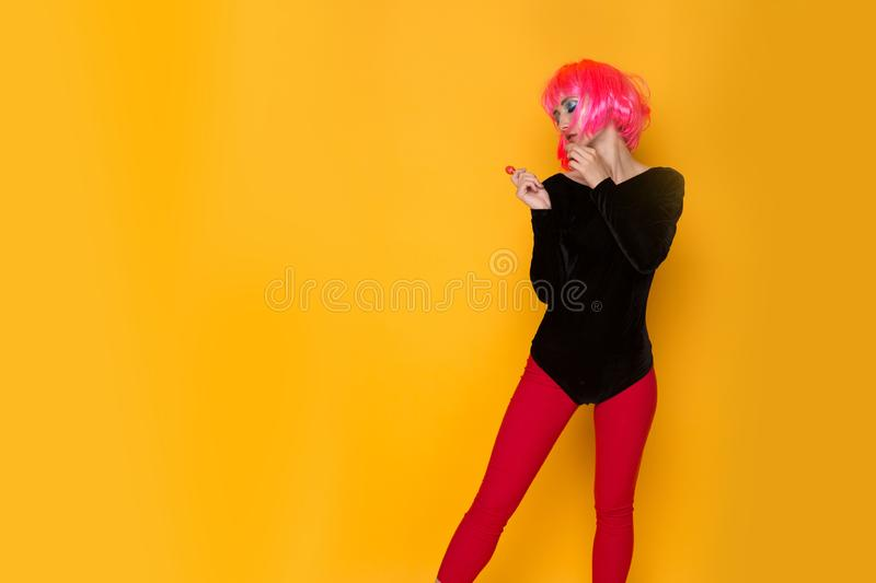 Pretty 90`s style woman in a black body and red tights holding candy standing at the yellow wall. stock photos