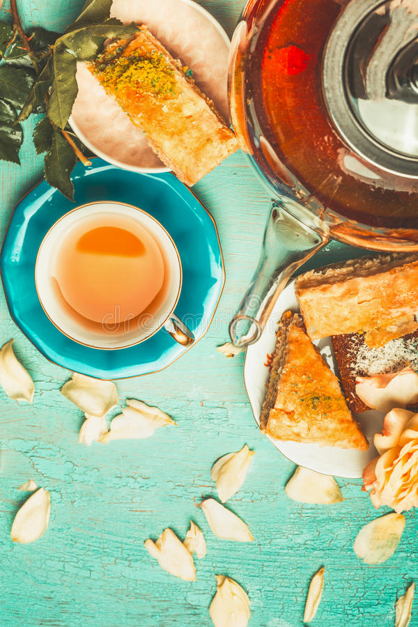 Pretty scene of tea brunch with cup and pot of tea , flowers and cake stock photography