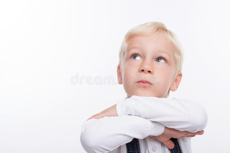 Pretty schoolboy is thinking about something. Cute boy is standing and dreaming. He crosses his hand and leaning his head on it. The boy is looking up pensively royalty free stock photo