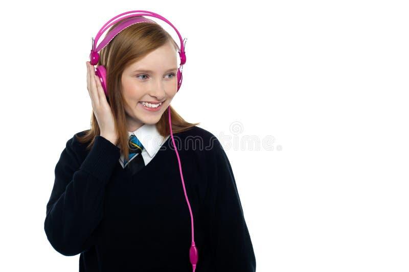 Pretty schoolgirl enjoying music. Student listening to music through headphones stock image