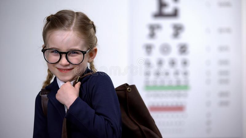 Pretty schoolgirl in glasses smile, awareness of complete eye exam before school. Stock photo royalty free stock image