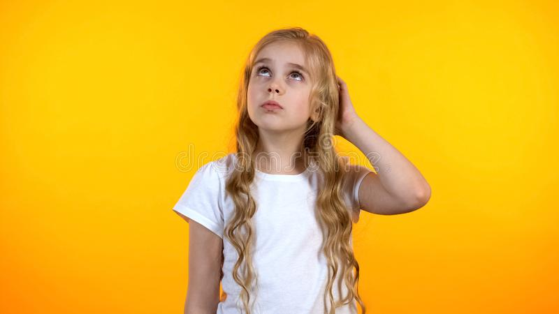 Pretty schoolgirl scratching head feeling uncertain about choice, lack of ideas. Stock photo stock photo