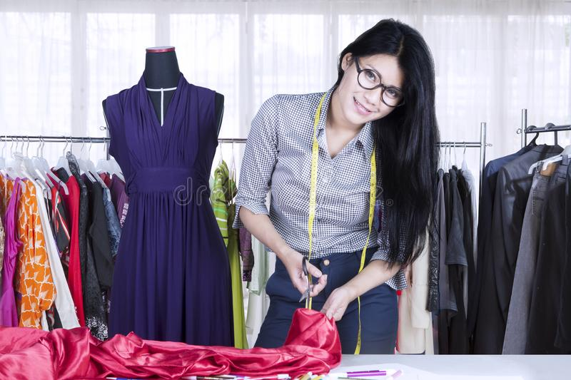 Pretty seamstress cutting a fabric in the workplace stock image